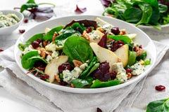 新鲜的梨,与菜绿色混合,核桃,蔓越桔的青纹干酪沙拉 健康的食物 库存照片