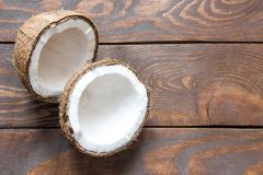 新鲜的椰子闯进在一个木台式视图的两部分与题字的一个地方 库存照片