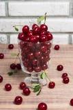 新鲜的樱桃在一张木桌上的一个玻璃碗结果实 免版税图库摄影