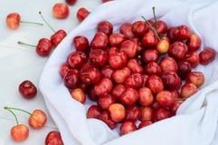新鲜的樱桃在长木凳背景的一条白色毯子 樱桃新鲜成熟 樱桃一牌照甜白色 库存图片