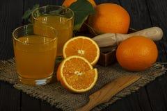 新鲜的橙汁用在一个玻璃碗的薄菏在一块黑暗的板材 在黑暗的背景的橙汁,顶视图,拷贝空间 免版税库存照片