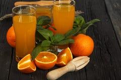 新鲜的橙汁用在一个玻璃碗的薄菏在一块黑暗的板材 在黑暗的背景的橙汁,顶视图,拷贝空间 免版税库存图片