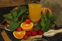 新鲜的橙汁用在一个玻璃碗的薄菏在一块黑暗的板材 在黑暗的背景的橙汁,顶视图,拷贝空间 库存照片