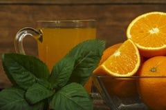 新鲜的橙汁用在一个玻璃碗的薄菏在一块黑暗的板材 在黑暗的背景的橙汁,顶视图,拷贝空间 库存图片