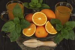 新鲜的橙汁用在一个玻璃碗的薄菏在一块黑暗的板材 在黑暗的背景的橙汁,顶视图,拷贝空间 免版税图库摄影