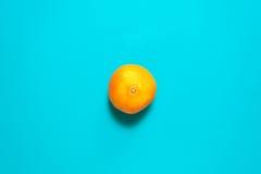 新鲜的橙色果子和汁液在蓝色背景桌上 库存照片