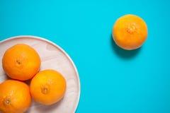 新鲜的橙色果子和汁液在蓝色背景桌上 库存图片