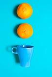 新鲜的橙色果子和汁液在蓝色背景桌上 免版税库存图片