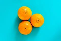 新鲜的橙色果子和汁液在蓝色背景桌上 图库摄影