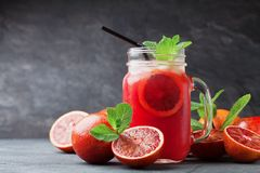 新鲜的橙色柠檬水饮料或汁装饰了在泥工玻璃瓶子的薄荷叶在黑背景 免版税库存图片