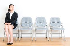 新鲜的毕业生夫人坐木地板椅子 免版税图库摄影