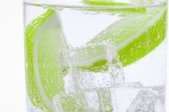新鲜的水多的石灰片断下沉入清楚的水 免版税库存图片