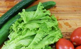 新鲜的水多的红色蕃茄、黄瓜和莴苣 免版税图库摄影