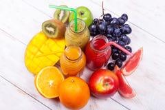 新鲜的汁液圆滑的人三瓶红色绿色橙色热带水果西瓜苹果计算机猕猴桃葡萄橙色芒果杉木苹果计算机Pomegra 免版税库存图片