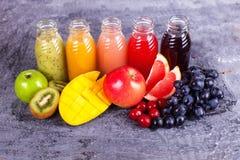 新鲜的汁液圆滑的人三瓶红色绿色橙色热带水果西瓜苹果计算机猕猴桃葡萄橙色芒果杉木苹果计算机Pomegra 库存照片