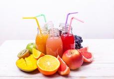 新鲜的汁液圆滑的人三瓶红色绿色橙色热带水果西瓜苹果计算机猕猴桃葡萄橙色芒果杉木苹果计算机Pomegra 库存图片