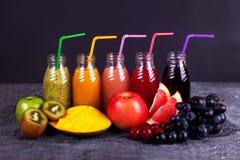 新鲜的汁液圆滑的人三瓶红色绿色橙色热带水果西瓜苹果计算机猕猴桃葡萄橙色芒果杉木苹果计算机Pomegra 免版税图库摄影