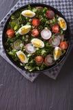 新鲜的沙拉有蛋、萝卜和草本垂直的顶视图 免版税库存图片