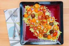 新鲜的沙拉板材用皱叶甘蓝、五颜六色的蕃茄和胡椒 图库摄影