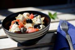 新鲜的沙拉用在黑碗的乳酪 库存照片