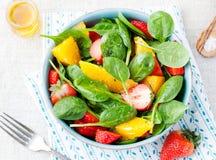 新鲜的沙拉用草莓、桔子和菠菜在一个碗在木背景 免版税库存照片