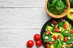 新鲜的沙拉用鲕梨、菠菜、蕃茄樱桃,希腊白软干酪和核桃在一块板材在白色木桌上 顶视图 免版税库存照片