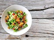 新鲜的沙拉蕃茄和混杂的绿色芝麻菜,mesclun,在木背景关闭的mache r 免版税库存照片