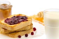 新鲜的法式多士用蜂蜜和果酱在一块白色板材用莓果在白色背景 免版税图库摄影