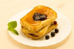 新鲜的法式多士用蜂蜜和果酱在一块白色板材用莓果 免版税库存图片