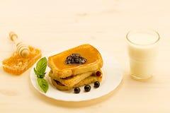 新鲜的法式多士用蜂蜜和果酱在一块白色板材用莓果 库存图片