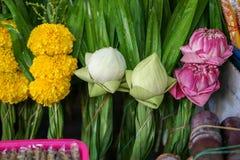 新鲜的泰国样式寺庙提供的花集合由白色和桃红色莲花,与绿色pandan叶子的黄色万寿菊制成 库存照片
