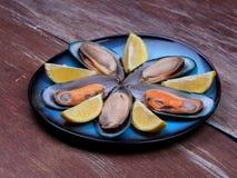 新鲜的淡菜和被扎营的柠檬在一蓝色platev设置了 库存照片