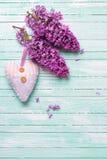 新鲜的淡紫色花和纺织品装饰心脏在绿松石p 免版税库存图片