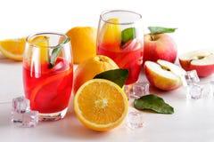 新鲜的混合糖浆用桔子、苹果切片和冰块 库存照片
