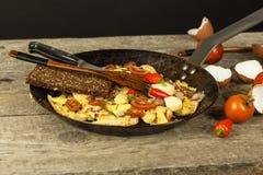 新鲜的炒蛋用火腿和辣椒在钢平底锅 一养育的传统早餐卡路里饭食 免版税库存图片