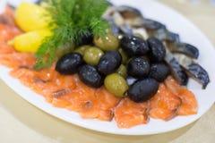 新鲜的烘烤狂放的桃红色三文鱼肉内圆角用黑橄榄和未加工的柠檬 免版税库存图片