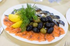 新鲜的烘烤狂放的桃红色三文鱼肉内圆角用黑橄榄和未加工的柠檬 免版税库存照片