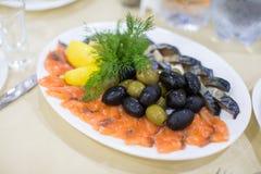新鲜的烘烤狂放的桃红色三文鱼肉内圆角用黑橄榄和未加工的柠檬 库存图片