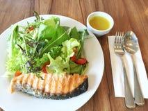 新鲜的烤三文鱼沙拉和色拉调味品、匙子和叉子在餐巾 免版税库存图片