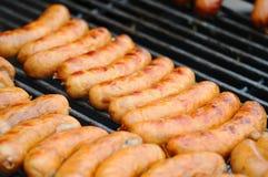 新鲜的烤户外在气体烤肉格栅的香肠和热狗 香肠特写镜头在格栅的 免版税库存照片