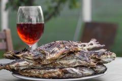 新鲜的烤鳟鱼堆在板材和一块玻璃的用r填装了 免版税图库摄影