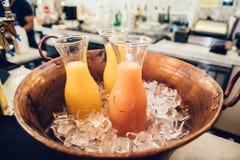 新鲜的热带桔子和被分类的汁液在玻璃瓶在冰在酒吧柜台在咖啡馆或餐馆 库存图片
