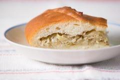 新鲜的热的俄国饼用圆白菜和肉 在pl的切的饼 免版税库存照片