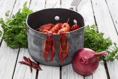 新鲜的煮沸的小龙虾用葱和荷兰芹在白色木背景 土气样式 新鲜的海鲜 蒸的小龙虾 免版税库存图片