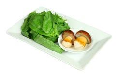 新鲜的牛肝菌蕈类蘑菇和菠菜在白色板材 免版税库存图片