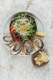 新鲜的牡蛎和日本沙拉顶视图服务用在白色石碗的切的和柠檬调味汁在washi日文报纸 图库摄影