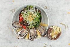 新鲜的牡蛎和日本沙拉顶视图服务用在白色石碗的切的和柠檬调味汁在washi日文报纸 库存照片