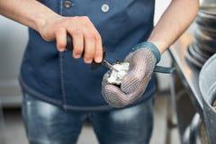 新鲜的牡蛎在一只手上对负开放与一把牡蛎刀子有牡蛎手套的 库存图片