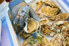 新鲜的牡蛎对负开放与手中的刀子 免版税库存照片