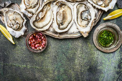 新鲜的牡蛎用柠檬和各种各样的调味汁在土气背景,顶视图,地方文本的 库存图片